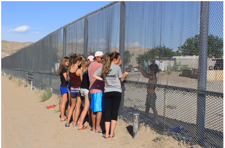 A cluster of people stand facing a tall chain-link fence. On the other side is a small child, fingers interlaced through the fence.