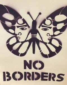 """Black spray paint and a stencil have been used to create a motif of a white wall. It's a butterfly with faces in the wings and the phrase """"No Borders."""""""