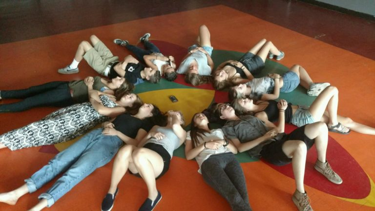 About a dozen people lay on their backs in a circle, heads touching and feet pointing out like rays of the sun.
