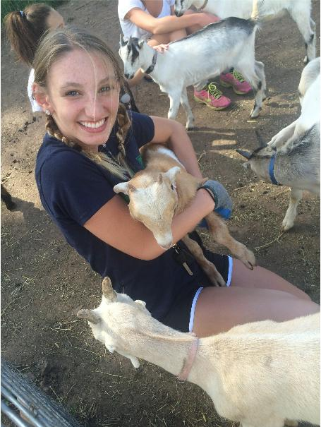 A teenager with two blonde braids kneels on dirt holding a baby goat.