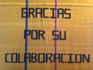 "A hand-woven tapestry says ""Gracias por su collaboration"" in black thread"