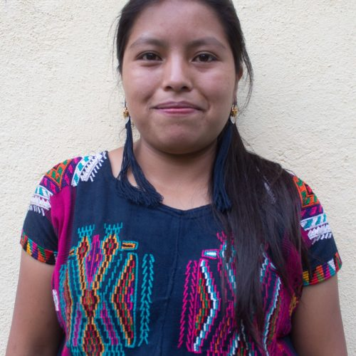 A headshot of Ana. She has tassel earrings, a chest-length side ponytail, and a colorful embroidered shirt.