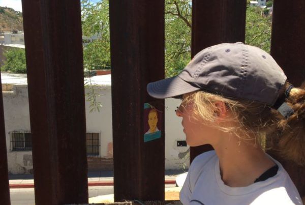 A woman in a baseball cap peers through the metal slats of the US/MX border