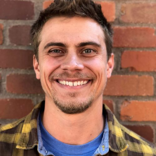 A white man in a yellow and black plaid shirt stands against a brick wall. His smile shows his top row of teeth and creases his cheeks.