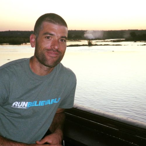 "a white man with a close-shaved head and beard stands in front of a lake at dusk. He is smiling with his lips closed and wearing a ""RUNbelievable"" shirt"
