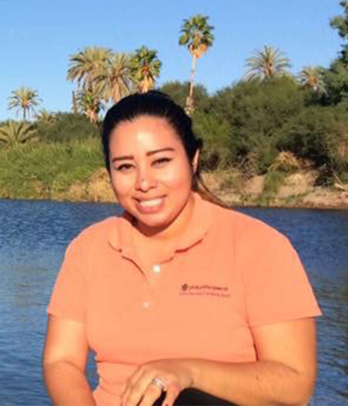 Sarai poses in front of a waterfront with palm trees. She's smiling at the camera and wearing a salmon polo shirt