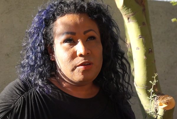 A headshot of Karolina. She has should-length curly purple hair, makeup, and a thoughtful gaze into the distance.