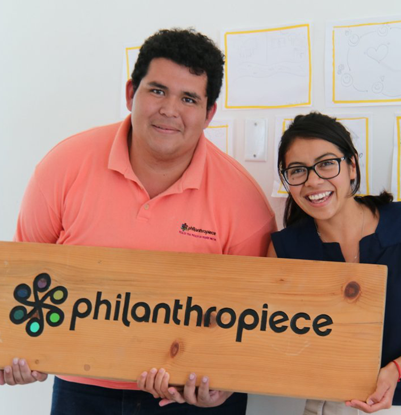 Two people smile at the camera while holding a wooden board engraved with the philanthropiece logo: six circles connected like a wheel in the center