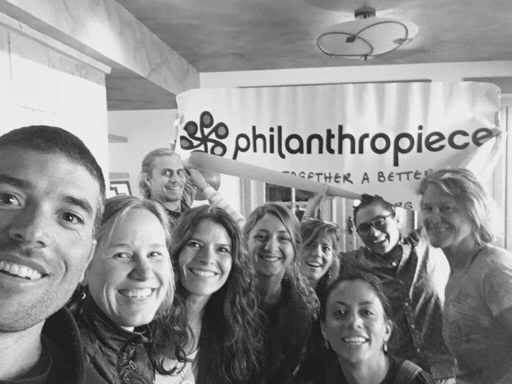 "The Colorado team takes a selfie in front of a large banner that says ""Philanthropiece, Piecing Together a Better World."""