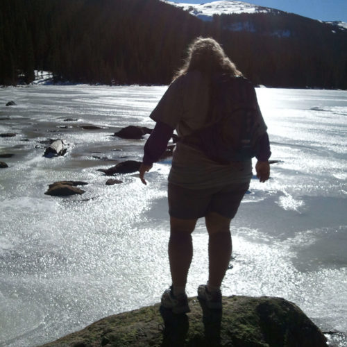 A picture of Doreen. She is shown standing on the shore of a mountain lake in silhouette