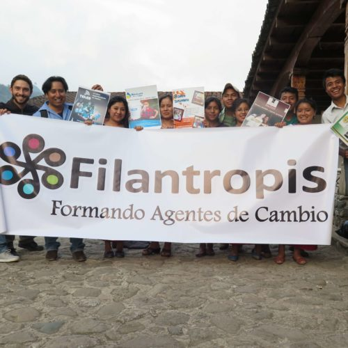 "A dozen people hold up a large banner that says ""Filantropis Formando Agentes de Cambio."""