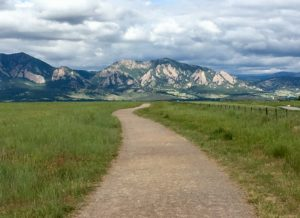 A dirt path lined with grass leads into the distance towards flatirons