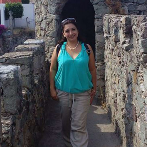 Marysabel stands in between two stone walls wearing tourist gear and smiling at the camera