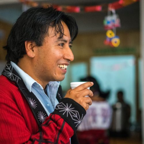 Ernesto smiles while holding a styrofoam cup and looking into the distance. He is wearing a red embroidered blazer and is shown from the shoulder up.