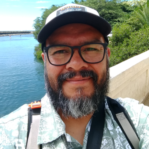 Ernesto takes a selfie on a concrete boardwalk. He has a baseball cap, big black glasses, and salt-and-pepper beard.