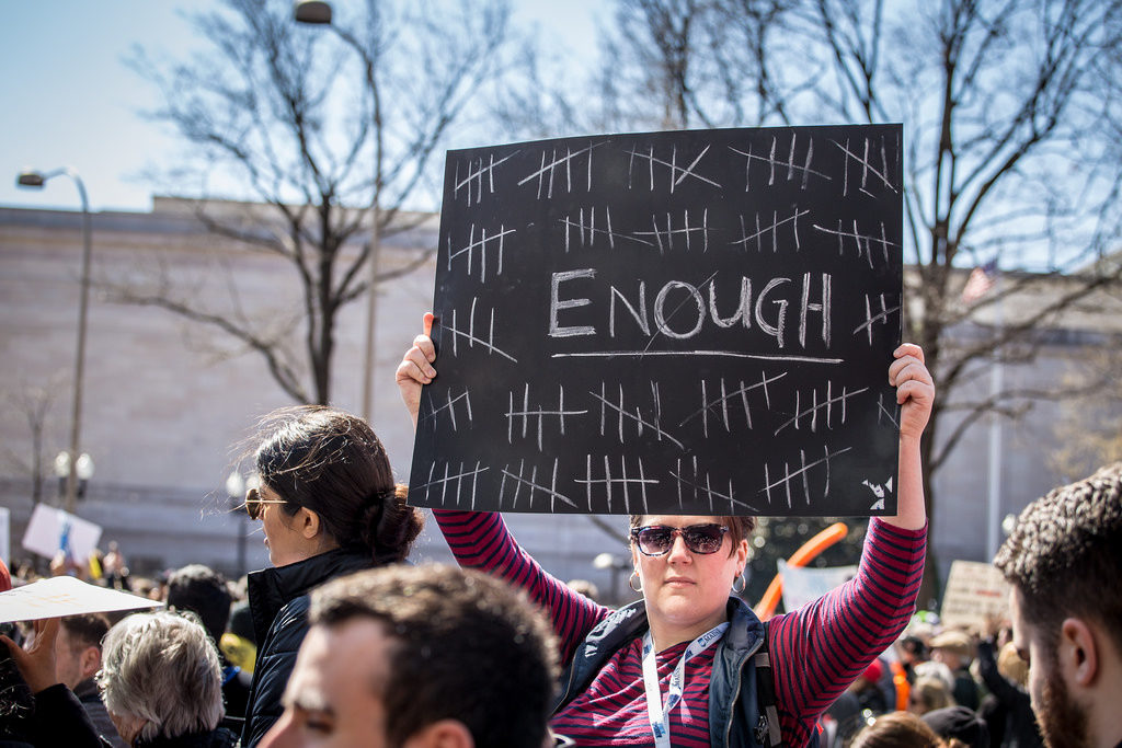 "A photo taken over the heads of march people reveals a woman holding up a sign that says ""enough"""