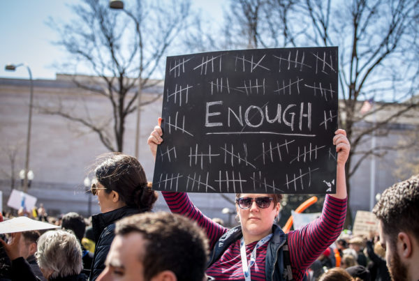 """A photo taken over the heads of march people reveals a woman holding up a sign that says """"enough"""""""