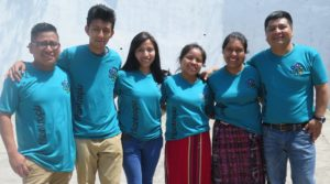 :Six people stand in a line with their arms linked. They are wearing matching blue Filantropis t-shirts.