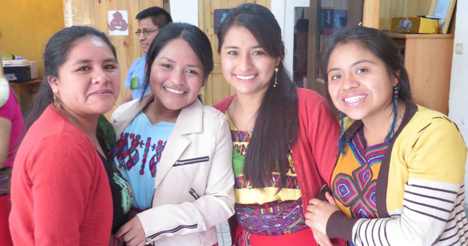 :Four women stand smiling at the camera with their arms linked. They are wearing a mix of traditional embroidered clothing and