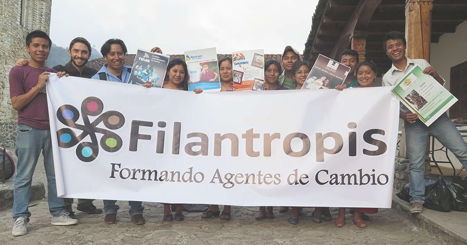 "A dozen of people stand on a cobblestone road holding a banner that says ""Filantropis. Formando Agentes de Cambio."""
