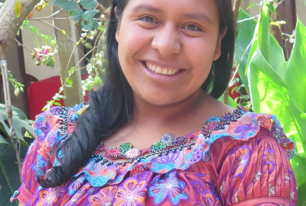 A headshot of Maria. She has an infectious smile, side-swept curled hair, light eyes, and a colorful embroidered blouse.
