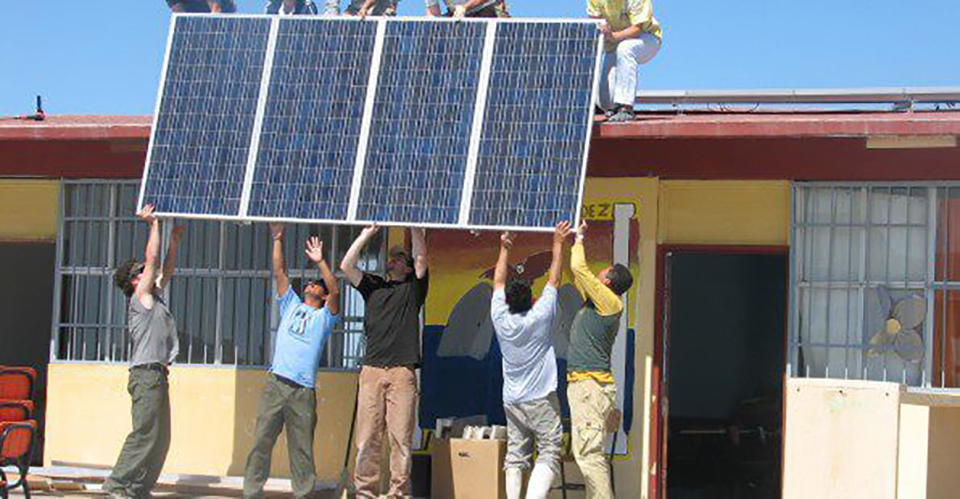 Five people are shown hoisting a solar panel up to five other people standing on the roof of a small building.