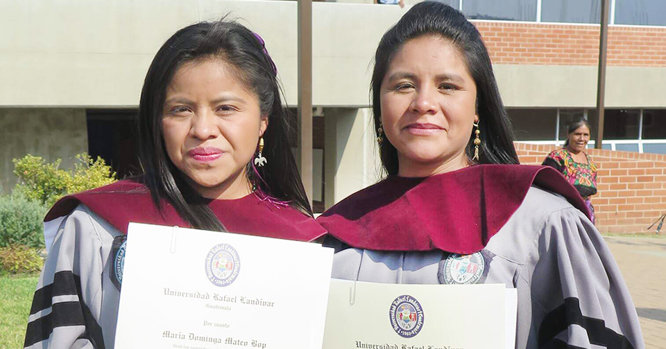 :Two women stand outside in lavender graduation gowns holding their diplomas