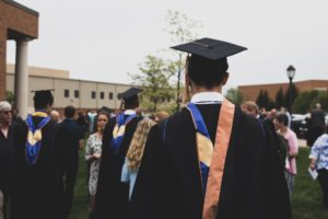 a person in a graduation cap and gown is pictured from behind. They are looking out onto a university courtyard full of milling people.