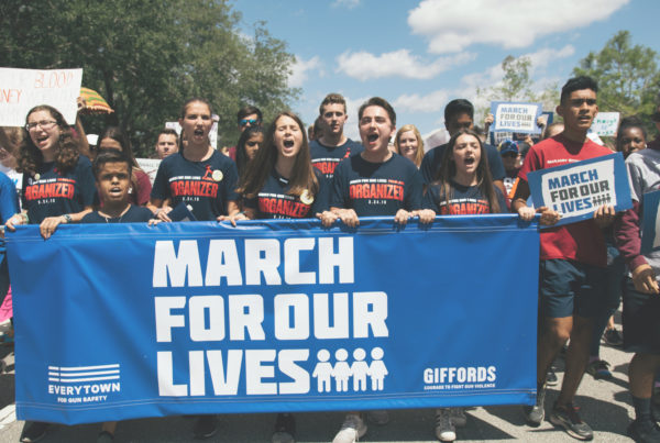 """A group of teenagers hold a blue sign with white text that says """"March For Our Lives."""" They are wearing matching navy shirts and are all mid-chant."""