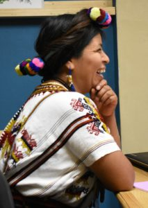 We see Dona Teresa from the right side as she stares at something outside the frame and laughs. She is wearing a colorfully embroidered white blouse, and there are colors textiles woven into her hair.