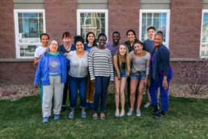 A dozen climate justice leaders stand facing the camera and smiling. They are outdoors in front of a building with three white-paneled windows.