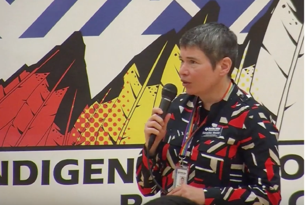 A person stands in front of an Indigenous People's Day banner and speaks into a microphone.