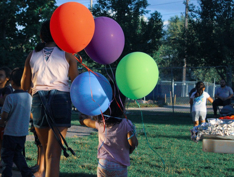 Two siblings walk away from the camera across a bright green lawn. They are holding a bouquet of balloons.