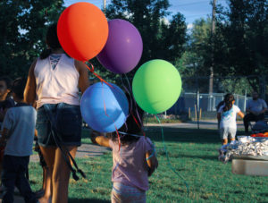 a young girl and her toddler-age sister walk hand and hand with a boquet of balloons.