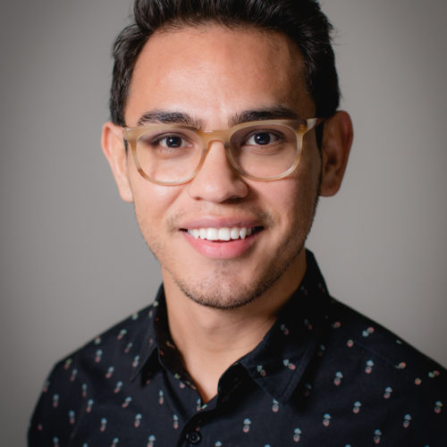 Professional headshot of Jose. He is a young Latino man wearing large, tan glasses and a dark navy button-up shirt.