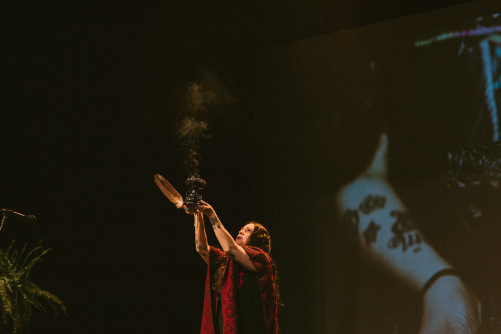 A woman wafts sage into the air during the 2019 Latinas LEAD conference.