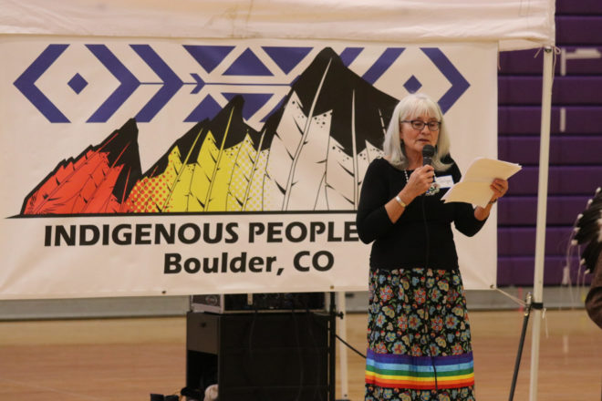 "a woman stands in front of a banner that says ""indigenous people's day boulder CO."" She is reading from a piece of paper and speaking into a microphone."