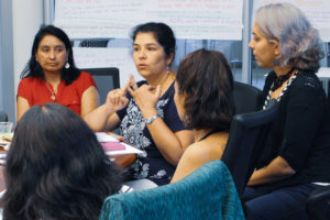 5 Latina women are pictured sitting around a table. One of them is talking, and the rest are listening intently.