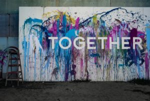 "Paint splashed banner with word ""together"" across the center."